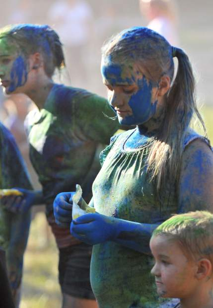 A group of Nevada County youth attempt to eat candy while covered from head to toe in the colors of the color run.