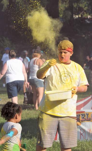 Ricky Frey tosses a handful of yellow at a youth during the color run.
