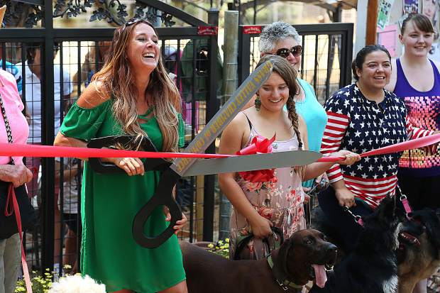 Local dog trainer Lauren Hayes smiles as she attempts to cut the ceremonial red ribbon in front of her Paws'itive Pals training location on Rough and Ready Highway in Grass Valley.