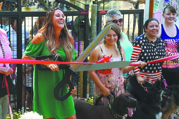 Local dog trainer Lauren Hayes, smiles as she attempts to cut the ceremonial red ribbon in front of her Paws'itive Pals training location on Rough and Ready Highway in Grass Valley.