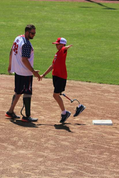 Cody Rice, left, congratulates a camper at the annual Wounded Warrior Amputee Softball Team Kids Camp. Rice has been a member of WWAST since 2014.