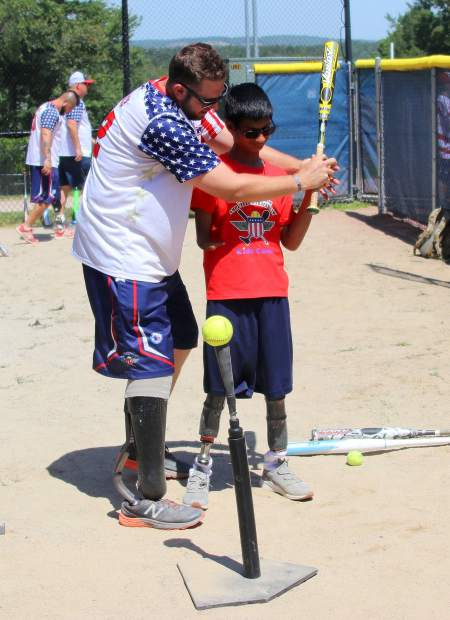 Cody Rice, left, works with a camper at the annual Wounded Warrior Amputee Softball Team Kids Camp. Rice has been a member of WWAST since 2014.
