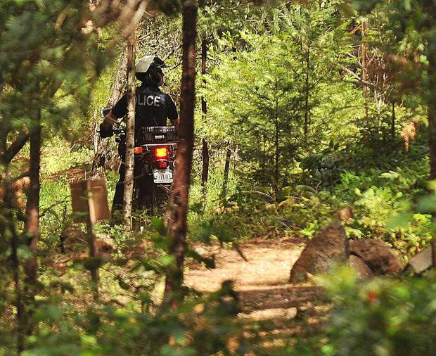 A Grass Valley Police Officer patrols the Wolf Creek Trail by motorcycle after hearing word of a homeless encampment discovered near the trail.