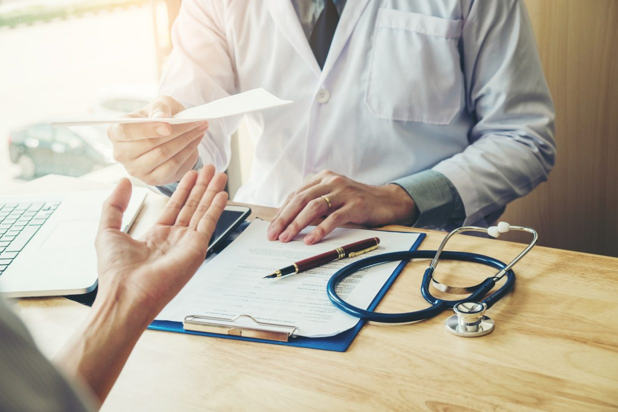 Doctor or physician writing diagnosis and giving a medical prescription to female Patient