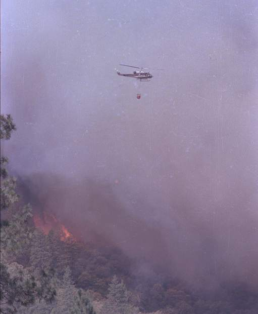 A helicopter dumps water on the 49er Fire in September 1988.