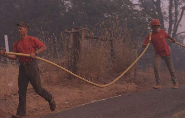 Residents help carry hose during the 49er Fire.