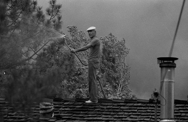 A Lake Wildwood resident sprays water on the roof his home during the 49er Fire in September 1988.