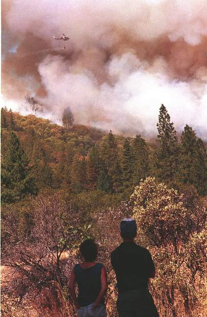 A couple watches the 49er Fire burn near Highway 49 and Reeder Ranch area, shortly after the fire broke out on Sept. 11, 1988.