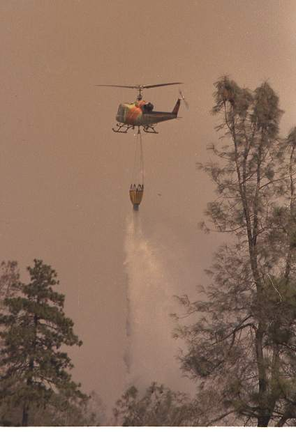 A helicopter makes a water drop on the 49er Fire.