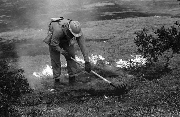A firefighters mops up hot spots during the 49er Fire.