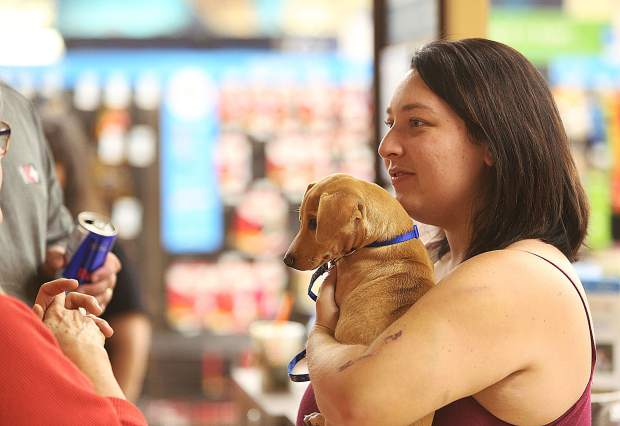 A prospective new owner holds a small dog she is interested in adopting during Saturday's Rescue For Pets Sake adoption event. All potential adoptees must first go through a background check and have their living space inspected beforehand.