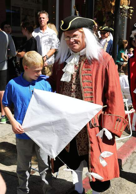 Benjamin Franklin of the Marching Masons poses with a young fan prior to the beginner the Sunday's Constitution Day Parade.
