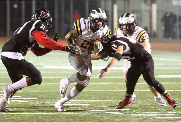 Nevada Union running back Jaxon Horne (21) gets hit from both sides by the Fairfield Falcons defense during Friday night's 21-0 road victory. Horne finished the game with 103 rush yards and a touchdown.