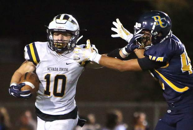 Nevada Union running back Hayden Lee (10) stiff arms River City opponent Adam MacDonald (48) during the Miners 53-21 win over the Raiders Friday night in Sacramento.