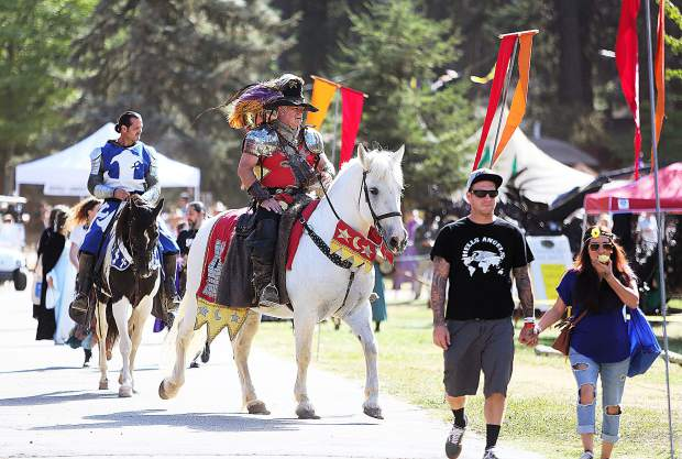 Sir Legion Blackheart rides above a rescued Percheron horse while the blue knight Sir Geoffrey rides along behind as they two lead people the arena for the jousting competition.