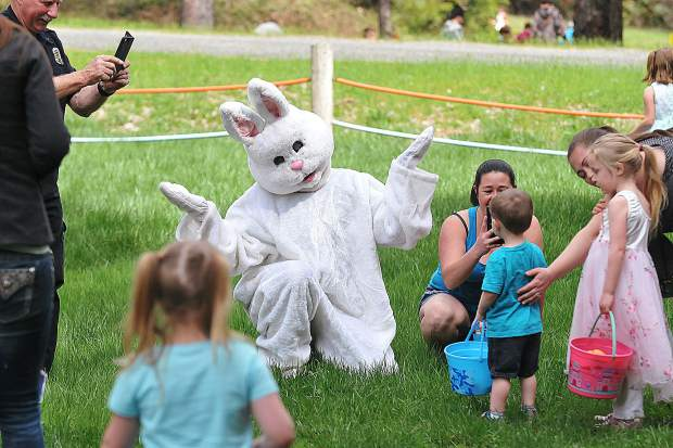 Accompanied by Chicago Park Firefighters, the Easter bunny tries to coax a reluctant group of youngsters to get their photo taken with it.