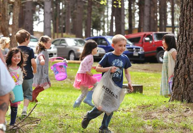 Children use Easter baskets, buckets, or bags to track down as many plastic Easter eggs hidden during the Nevada Irrigation District's event at Orchard Springs Campground in Chicago Park Saturday. Special prize eggs gave the children more incentive to catch em all.