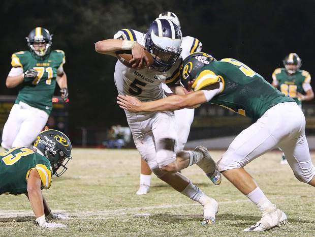 Dawson Fay (5) is met by defenders as he carries the ball Friday against the Placer Hillmen.