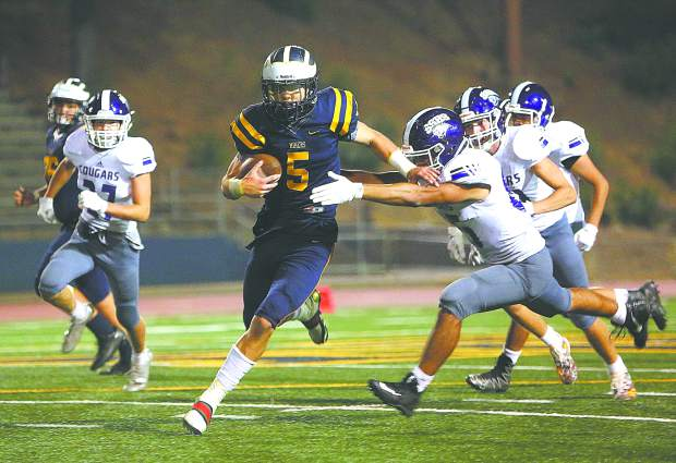 Nevada Union running back Dawson Fay (5) runs the ball on the option during late game Miner football action against the Spanish Springs Cougars Friday night at Hooper Stadium.
