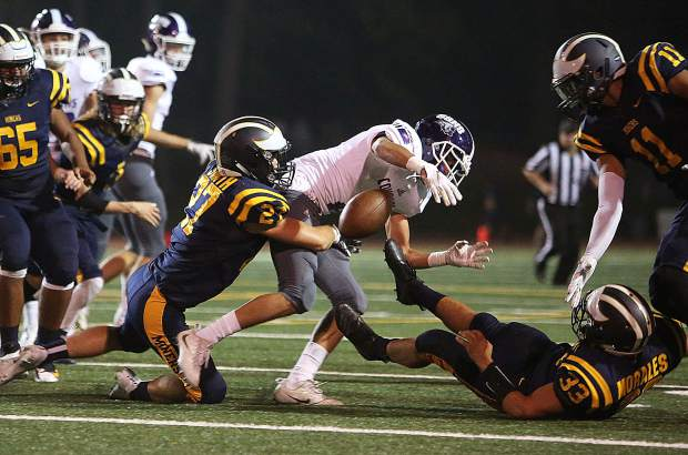 The Nevada Union defense, including Kaleb Smith (27) and Duke Morales (33) force a fumble during Friday night's home opener.