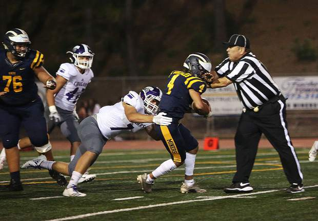 Nevada Union running back Isreal Gonzales gains ground before running into a referee on the field.