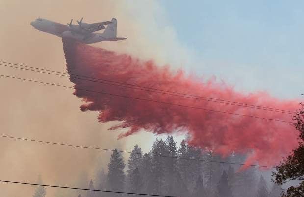 A Coulson C-130Q air tanker makes a long, low drop onto the vegetation of a meadow near Bitney Springs Road in efforts to slow the progress of the Lobo Fire.