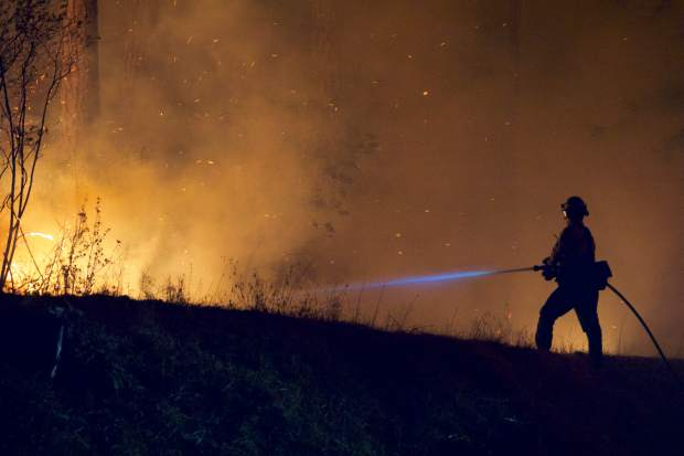 A firefighter sprays water onto the McCourtney Fire burning off of McCourtney Road and Polaris Drive.