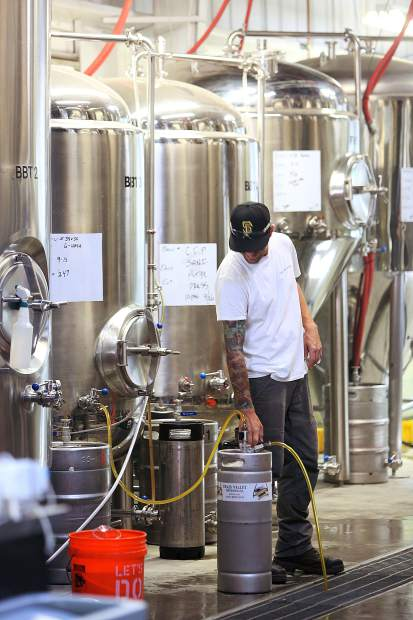 Grass Valley Brewing Co. brewer Chris Chapel works on refilling a keg of Grateful Haze Hazy IPA, one of the more popular beers available.