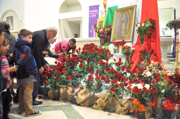 Parishioners approach images of the Virgin Mary with offerings of roses and flowers Tuesday night in St. Patrick's Catholic Church. The roses are symbolic of the flowers that Juan Diego picked at the request of the Virgin Mary as a way to validate the apparitions. Carrying the roses in his tunic, Diego dropped the flowers at the feet of the local bishop, and the image of Our Lady of Guadalupe appeared on the cloth. The tunic exists to this day and is on display in the basilica at Tepayac where 22 million Catholics make pilgrimages to each year.