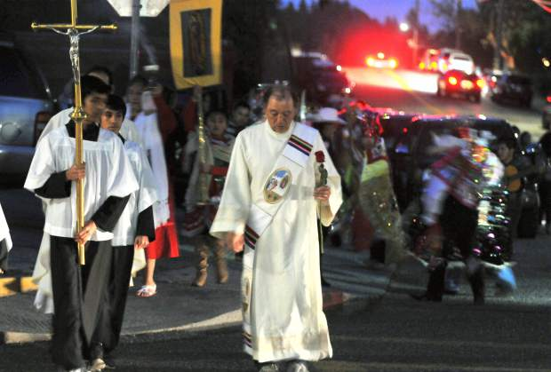 Deacon Richard Soria approaches St. Patrick's Catholic church with a rose offering during the celebration of Our Lady of Guadalupe Tuesday night.