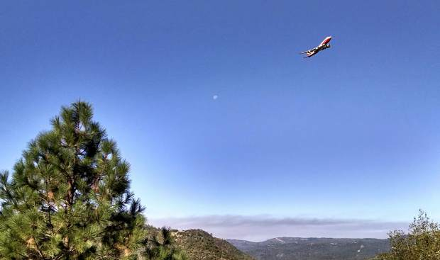 After tanker drop on the Lobo fire Monday, a plane climbs out over South Yuba with the moon in background.