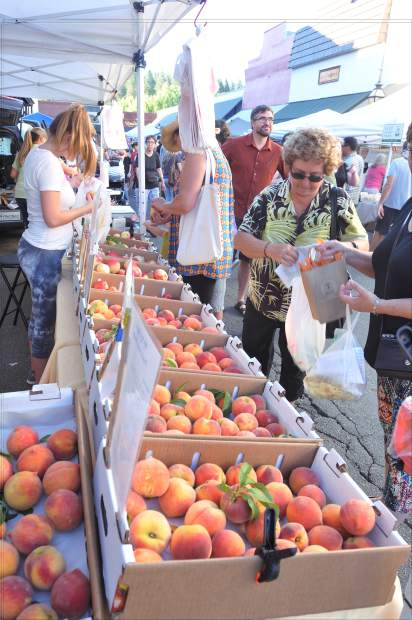 Shoppers pick from fresh peaches and other fruits available from Urbina Family Farms at a 2017 Thursday Night Market.