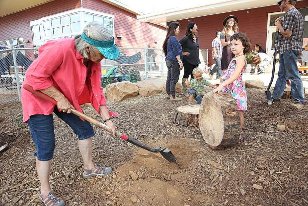 Mrs. Shan Kendall, Yuba River Charter's hand work and farm school program teacher, gets some help from 6 year old Oriya Egozi as the school works on various projects around campus during Friday's Harvest Festival.