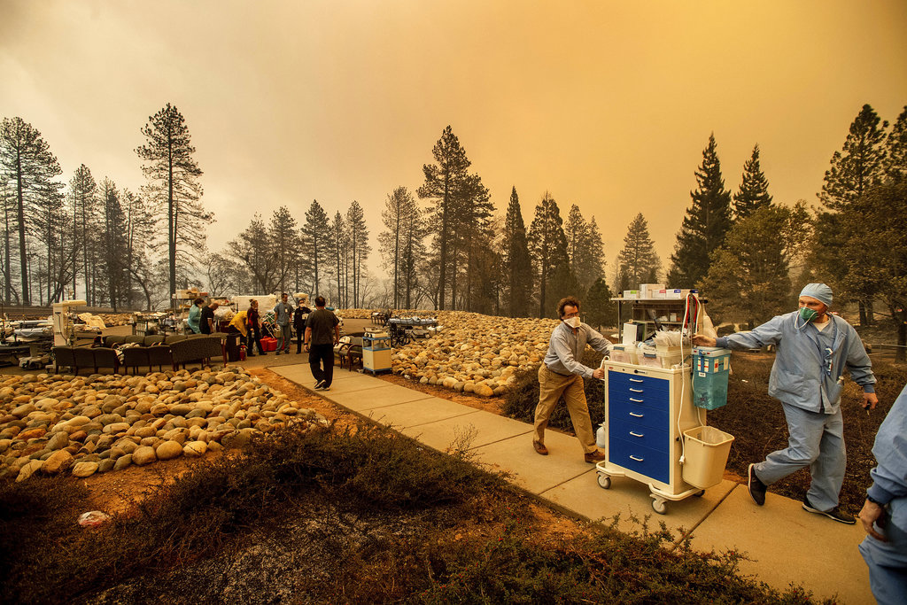 Medical workers move equipment from a makeshift emergency room while the Feather River Hospital burns as the Camp Fire rages through Paradise, Calif., on Thursday, Nov. 8, 2018. Tens of thousands of people fled a fast-moving wildfire Thursday in Northern California, some clutching babies and pets as they abandoned vehicles and struck out on foot ahead of the flames that forced the evacuation of an entire town. (AP Photo/Noah Berger)