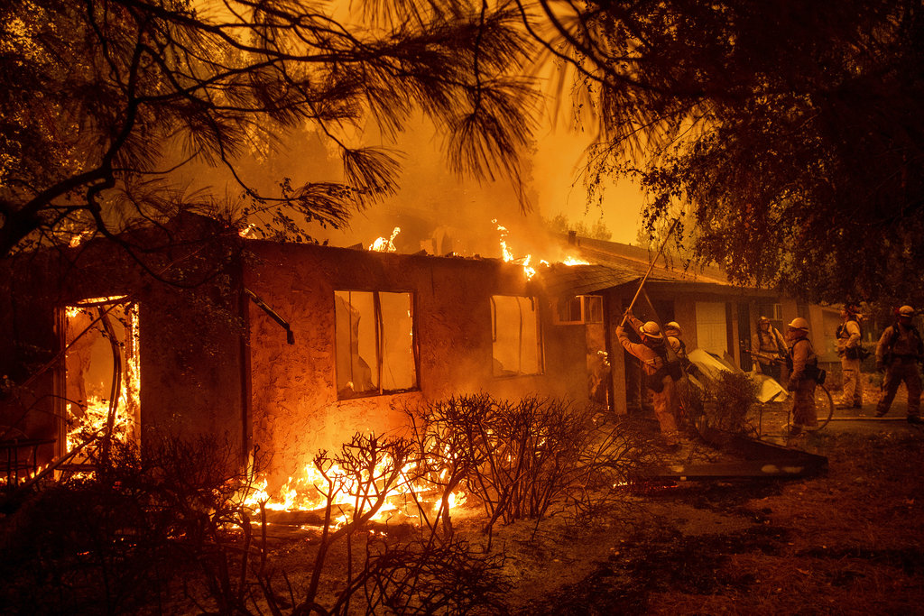Firefighters work to keep flames from spreading through the Shadowbrook apartment complex as a wildfire burns through Paradise, Calif., on Friday, Nov. 9, 2018. (AP Photo/Noah Berger)