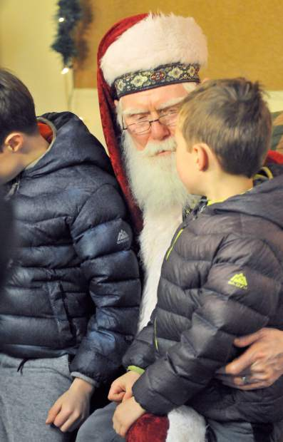 Santa Claus hears a pair of children's Christmas wishes in the basement of the Nevada City Methodist Church during Wednesday's Victorian Christmas.