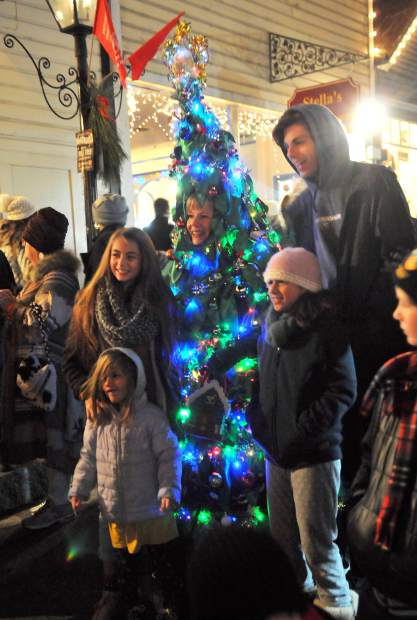 A family poses with a woman dressed as a Christmas tree while walking along Broad Street during Wednesday's final Victorian Christmas of 2017.