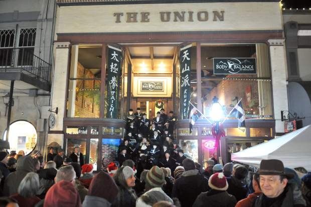 Cornish Christmas goers gather in front of The Union building on Mill Street where the Cornish Carol Choir readies to sing another song Friday night during the final Cornish Christmas of the year.