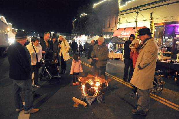 Folks warm up by the fire during Friday night's final Cornish Christmas event of the year. A series of diferent fire barrels around the event helped keep folks warm.