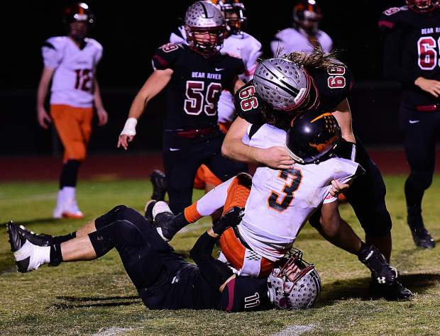 Bear River's Trae Nix (66) and Logan Jenkins (11) take down a Foothill ball carrier.