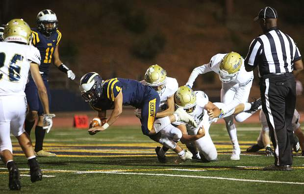 Isreal Gonzales (4) dives to pick up extra yards as he is taken down by a slew of Napa defenders.