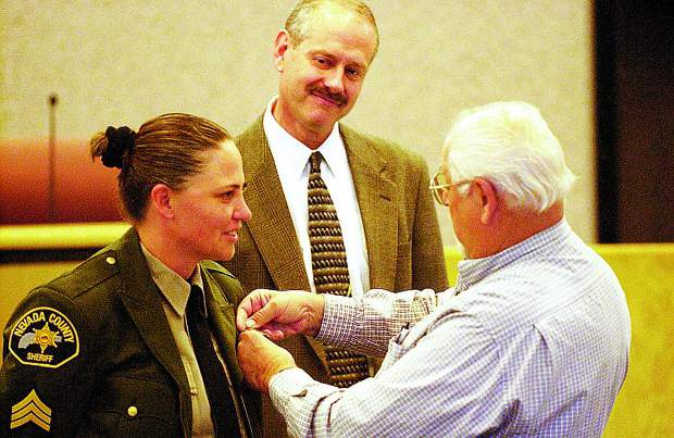 Sheriff Keith Royal observes as former Nevada County Deputy Sheriff and Nevada City Police Chief Jim Moon Sr., right, pins a sergeant badge onto his daughter, Shannan Moon, during a 2006 ceremony at the Rood Center. Moon was the county's first woman promoted to the rank of sergeant, lieutenant, captain, and now elected as sheriff.