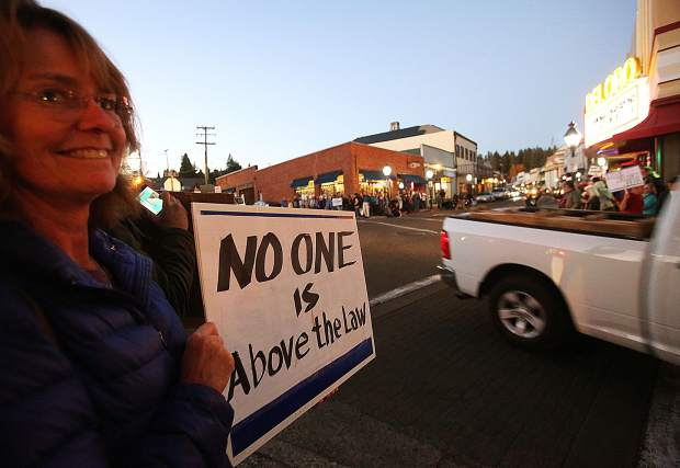 Folks hold signs around the intersection of Mill and Neal Streets in downtown Grass Valley.
