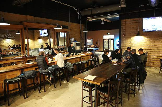 Customers mingle in the new space of 1849 Brewing Co. Monday night in Grass Valley's Glenbrook Basin. The brewery is using space vacated from The Union newspapers' former printing space.