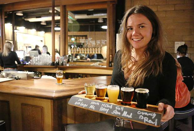 Eleanor Kelly holds a flight of five different 1849 Brewing Co. beers on tap Monday night. The brewery is now open everyday at 11 a.m.
