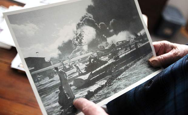 Lou Conter holds a photo showing the wreckage of Pearl Harbor from his home in Grass Valley Wednesday. This is the first time in over 25 years that Conter, or any survivors of the USS Arizona, will not be in attendance of today's Pearl Harbor Remembrance Day.