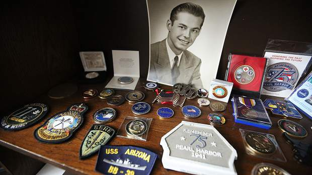 A high school graduation photo of Lou Conter is surrounded by a portion of the many medals and patches marking his accomplishments from decades in the armed services.