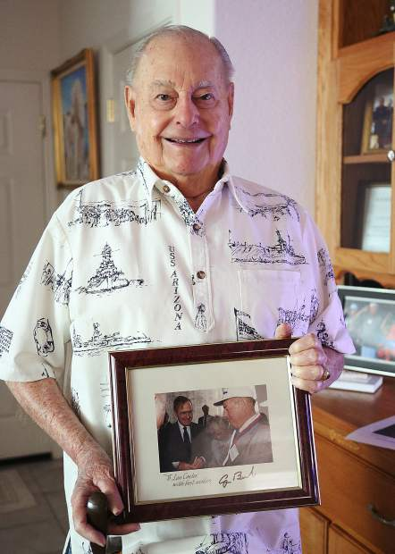 WWII and USS Arizona survivor Louis A. Conter, holds a photo of him and then President George H.W. Bush, taken during a previous Pearl Harbor Remembrance Day. Bush was the only sitting president to attend Pearl Harbor Day.