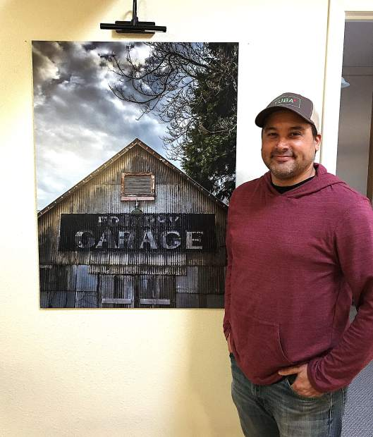 Kial James stands next to his photo of the Miners Foundry garage, part of a private collection in a Nevada City business.