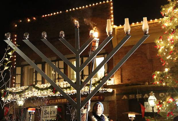 Members of Chabad of Grass Valley help to light the menorah during Thursday evening's ceremony in celebration of the Jewish holiday of Hanukkah at Robinson Plaza. This is the third menorah lighting ceremony to be held in downtown Nevada City.